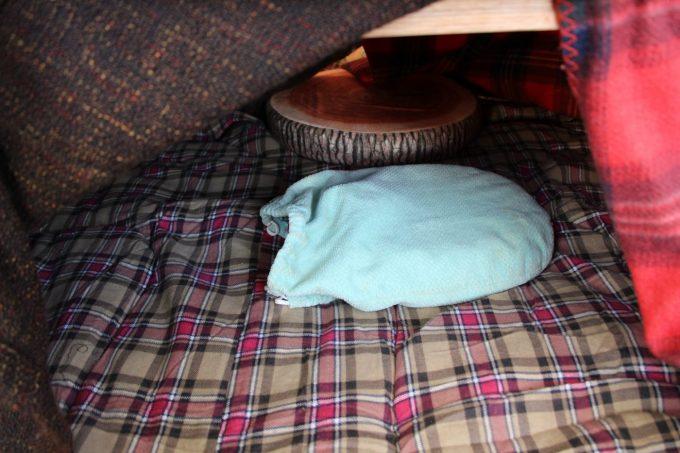 キャンプで簡易コタツをするには湯たんぽを中に入れます。